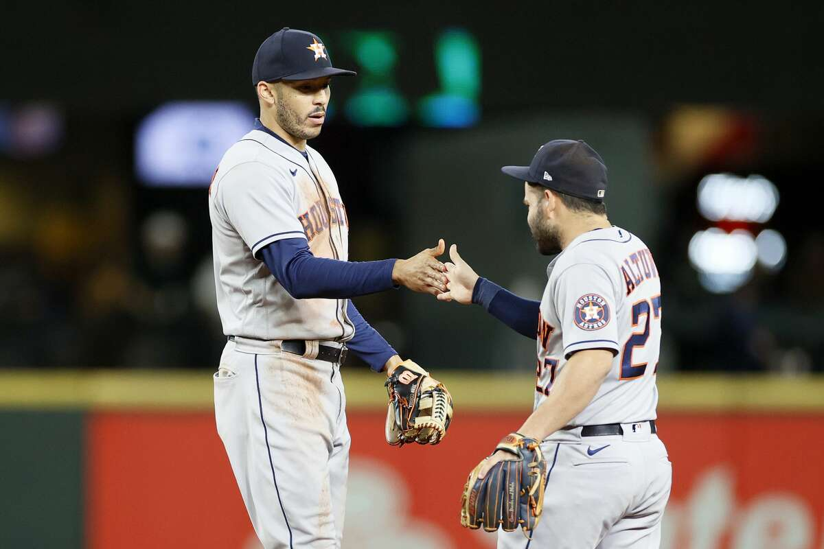 SEATTLE, WASHINGTON - AUGUST 30: Jose Altuve #27 and Carlos Correa #1 of the Houston Astros high five after defeating the Seattle Mariners 4-3 at T-Mobile Park on August 30, 2021 in Seattle, Washington. (Photo by Steph Chambers/Getty Images)
