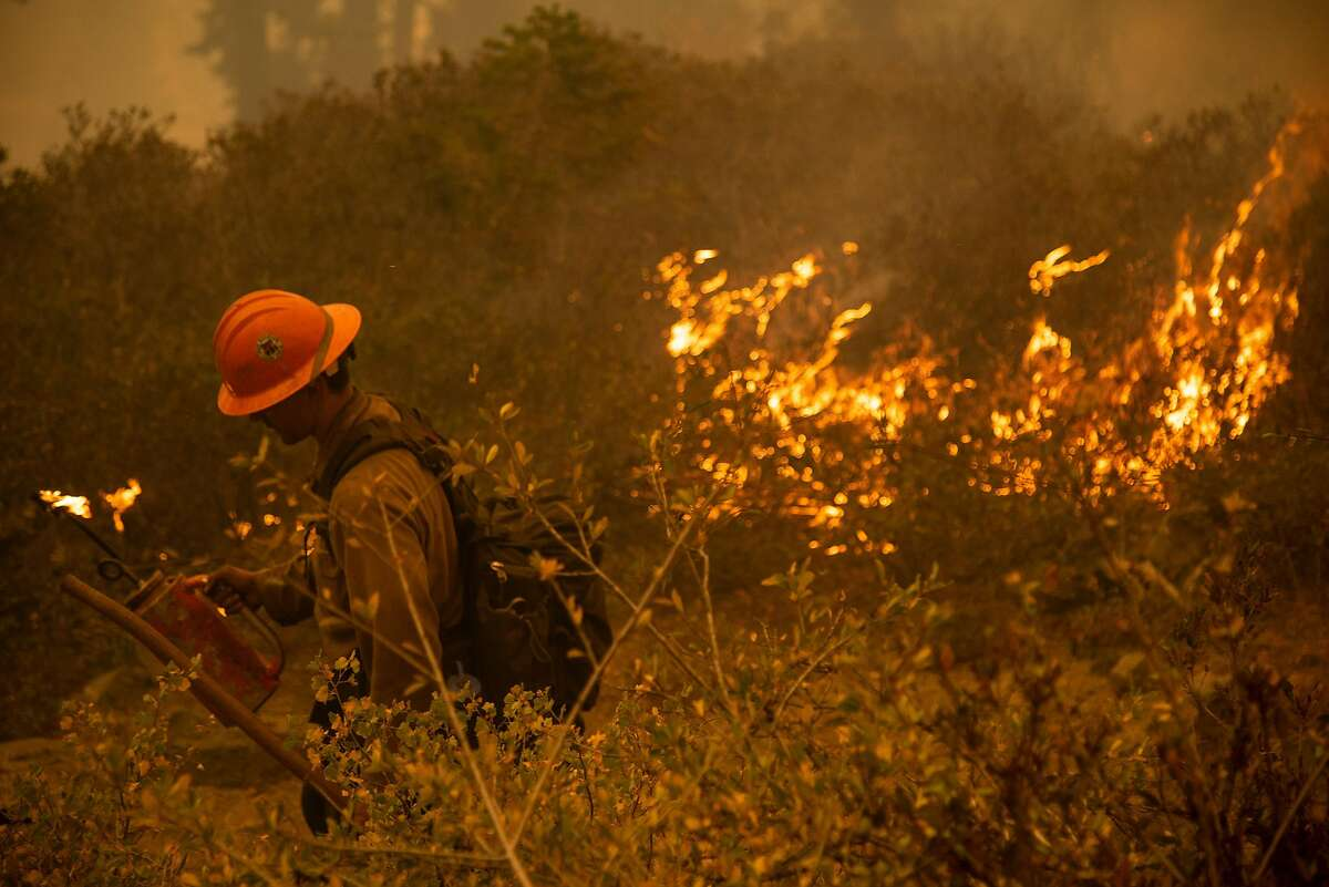 Mark Salerno of the Iron Mountain Hand Crew uses a drip torch to create a fire break around Echo Summit Lodge in order to protect it from flames of the Caldor Fire near South Lake Tahoe, Calif.