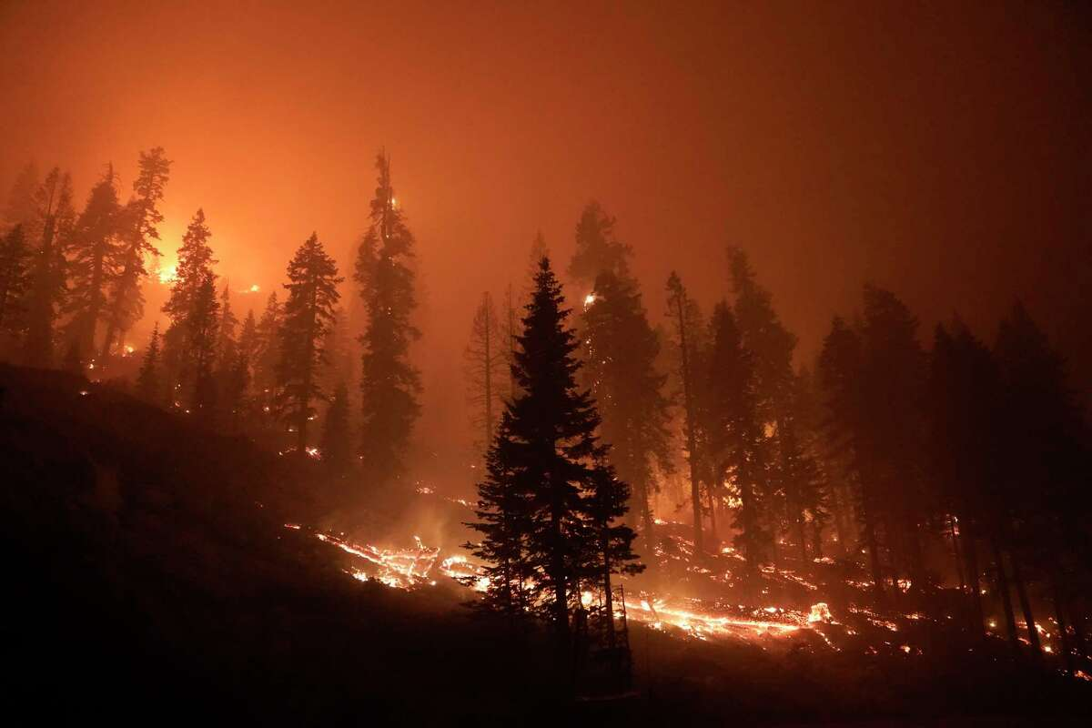 The Caldor Fire burns near structures in South Lake Tahoe, Calif., Monday, Aug. 30, 2021. As the winds returned this week, the Caldor Fire roared over the Sierra crest and bore down on the southern end of Lake Tahoe.