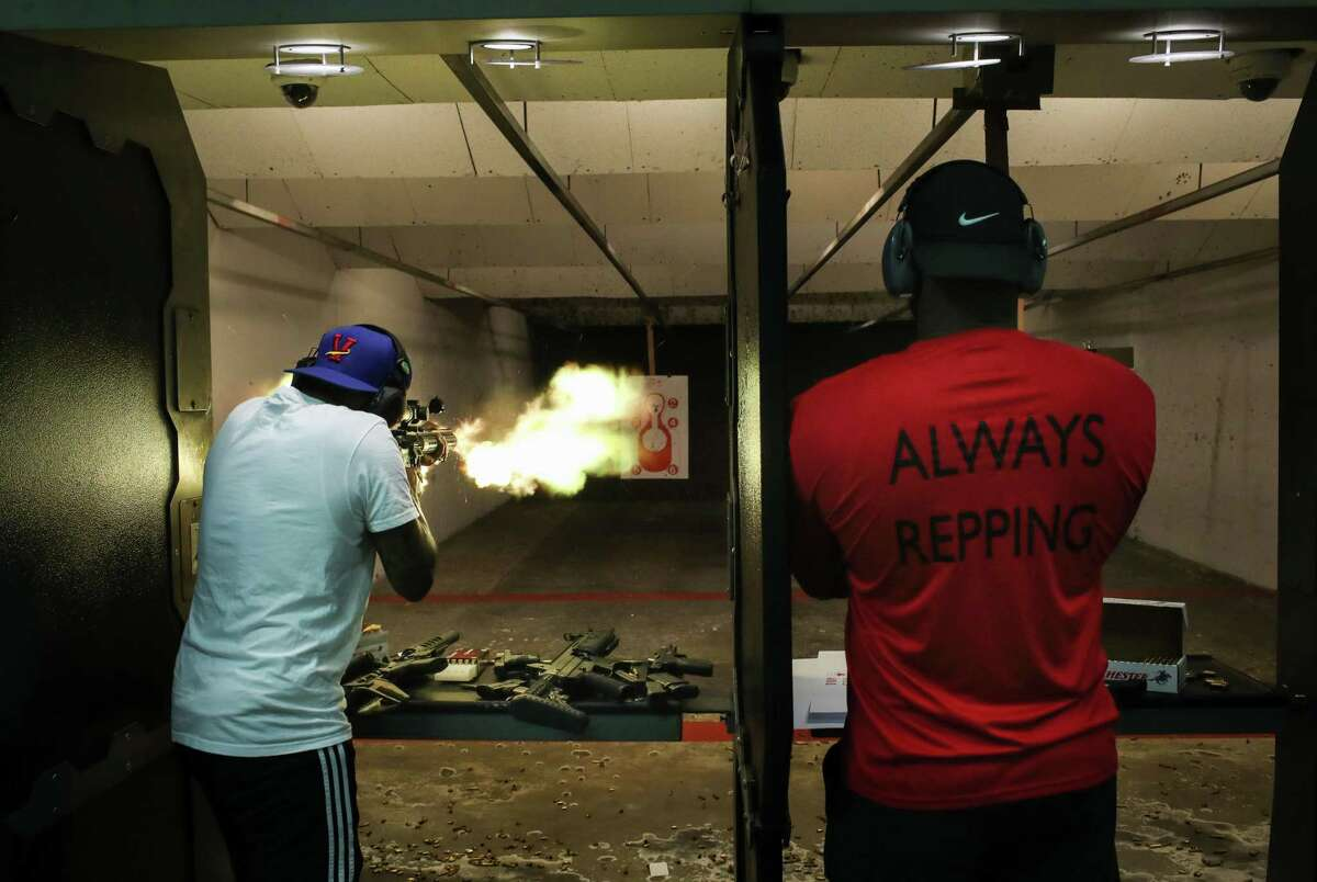 """Roshad Duncan, left, and Dwight Harrell shoot a variety of pistols and rifles Monday, Aug. 30, 2021, at Top Gun Range in Houston. """"This is Lego blocks for men,"""" Duncan said of customizable AR-style rifles."""