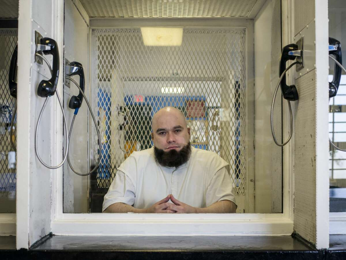 """John Henry Ramirez, who is on death row, in the visitation area of the Allan B. Polunsky Unit prison in Livingston, Texas, Aug. 25, 2021. Ramirez's federal lawsuit claims that the state's refusal to allow his pastor to lay hands on him during his execution burdens his free exercise of religion at the exact moment """"when most Christians believe they will either ascend to heaven or descend to hell - in other words, when religious instruction and practice is most needed."""" (Matthew Busch/The New York Times)"""