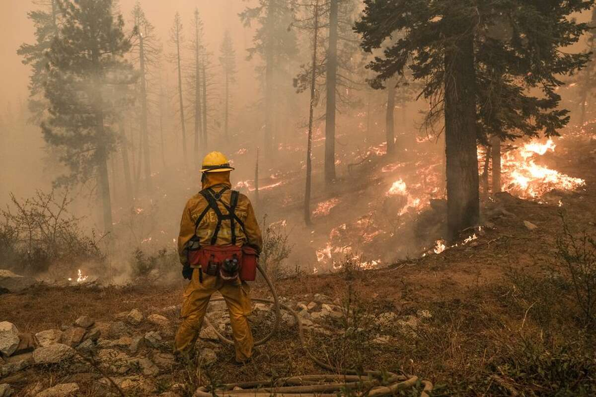 A firefighter monitors a fire threatening the Echo Summit Lodge during the Caldor Fire near Echo Lake, California, on Monday.