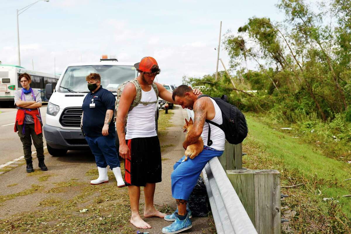 Evacuees console each other after arriving in unincorporated Jefferson Parish, La., via the Louisiana Army National Guard and a high water vehicle coming from the town of Jean Lafitte, La. on Monday, Aug. 30, 2021 after Hurricane Ida swept through the region a day earlier.