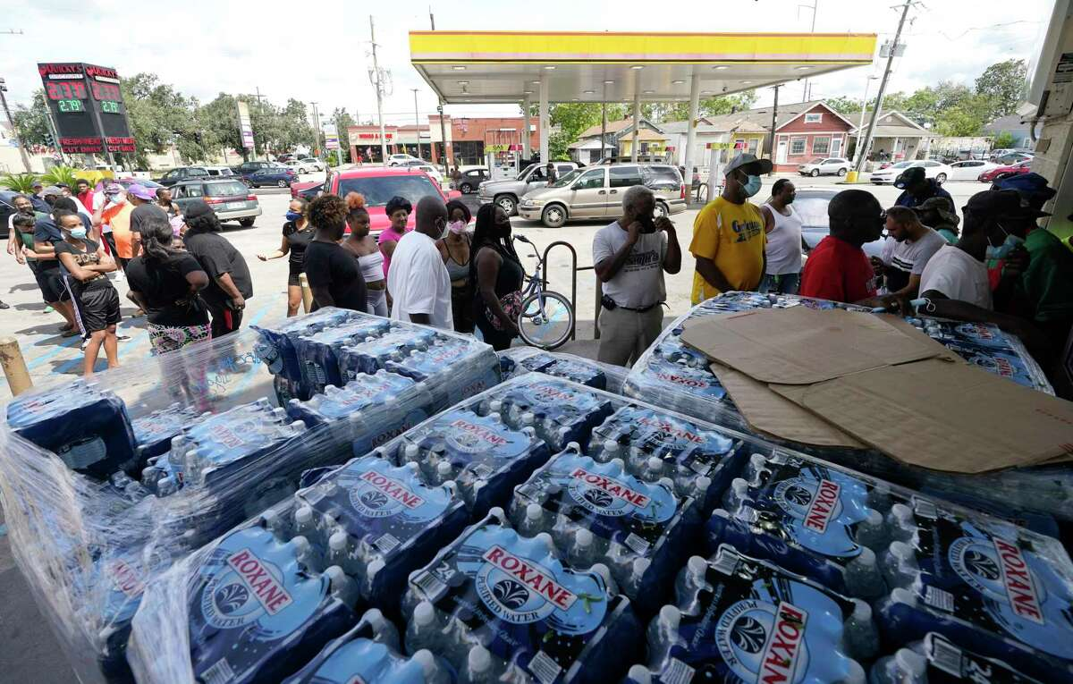 Customers stand in line to shop at a convenience store with no electricity in the aftermath of Hurricane Ida knocked out power in the area, Monday, Aug. 30, 2021, in New Orleans, La.