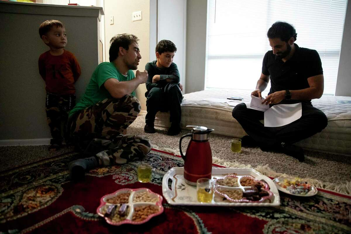 Farooq Moeen Shah speaks with his Catholic Charities case worker, Mustafa, flanked by two of his five children.