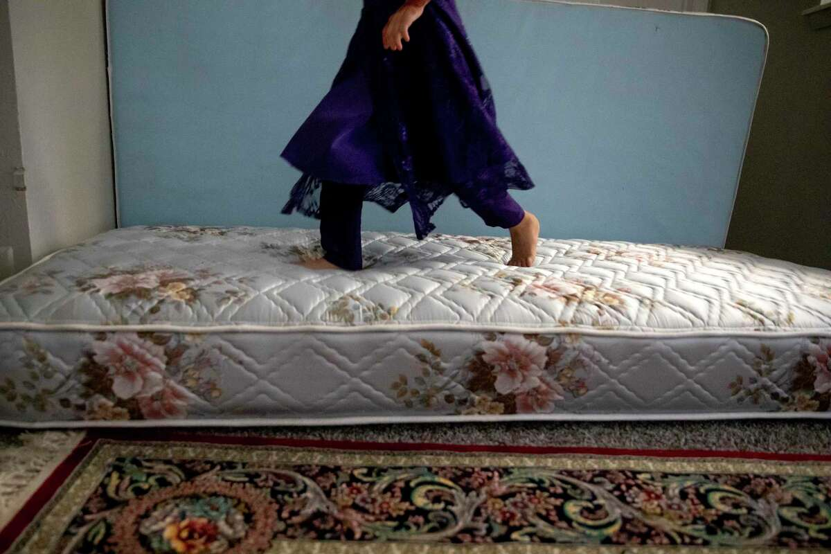 Sayeera Moeen Shah plays on donated mattresses in her dad's apartment. Sayeera, her mom and four siblings have joined her father in San Antonio after fleeing Afghanistan as the Taliban took control of the country.