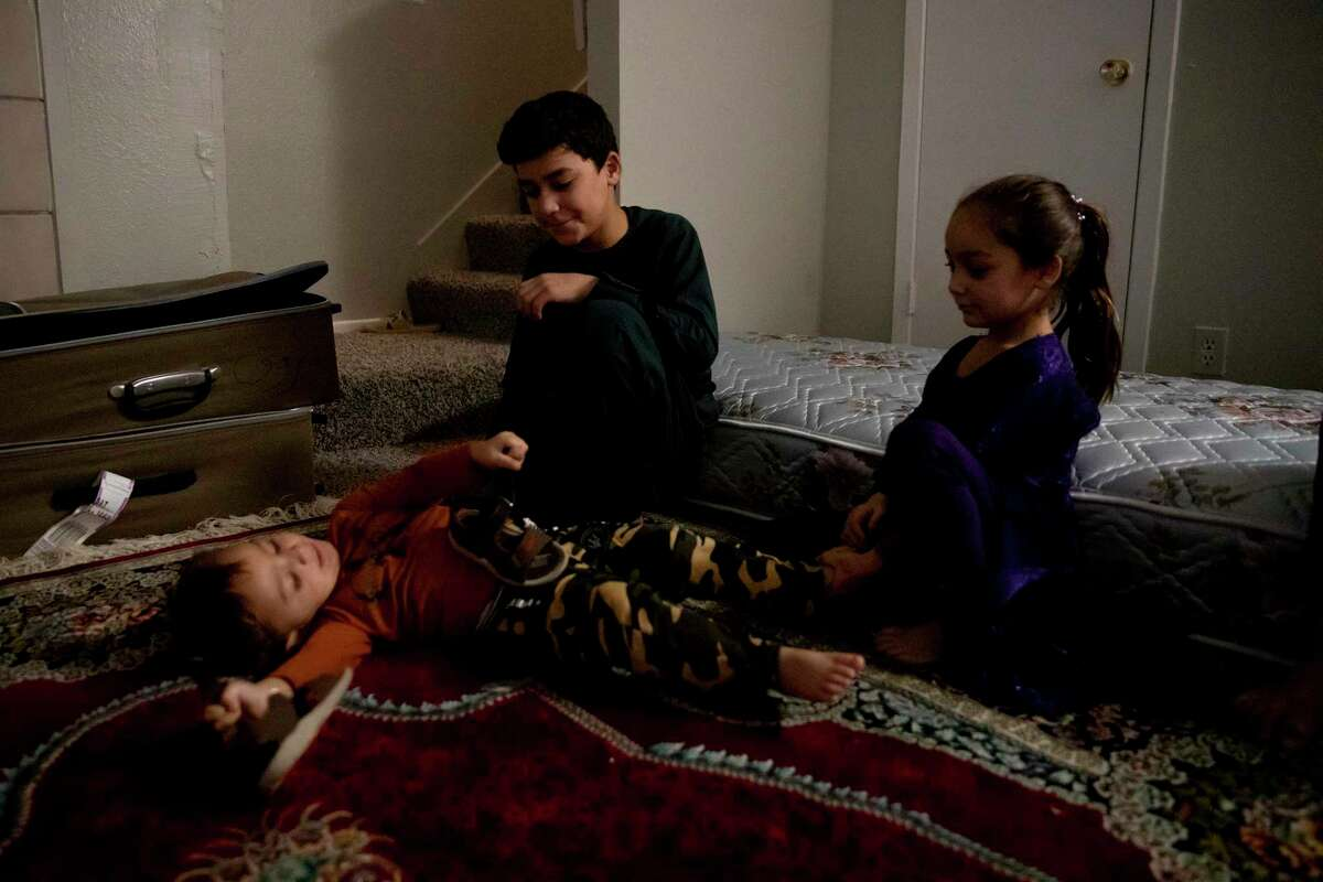 Imal Moeen Shah and his siblings, Sayeera and Tasal, sit with each other while their father, Farooq Moeen Shah, talks with friends. The siblings and their mom have joined their father in San Antonio from Afghanistan after fleeing the Taliban.