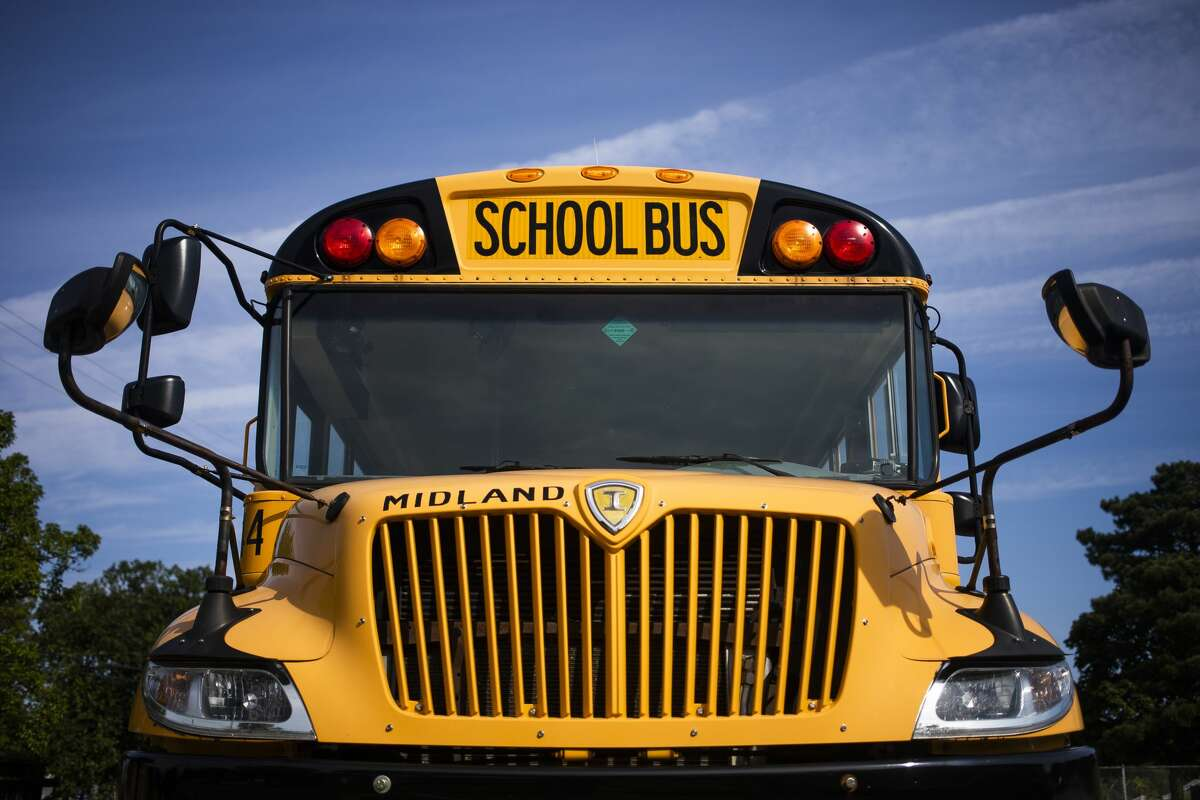 A bus is parked outside of Midland High School with a sign advertising that Midland Public Schools is looking to hire bus drivers Tuesday, Aug. 31, 2021. (Katy Kildee/kkildee@mdn.net)