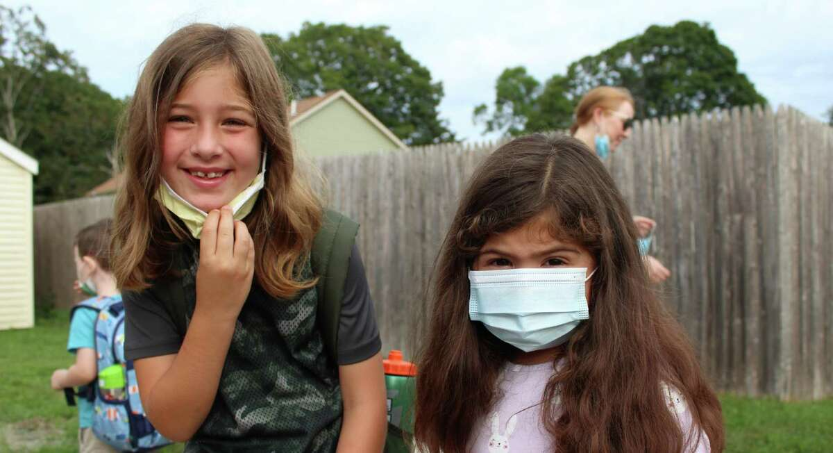 From left, Old Saybrook students Jade Gerbers, a second-grader, and Brityn Gerbers, pre-kindergartener, were all smiles Tuesday on their first day back to classes.