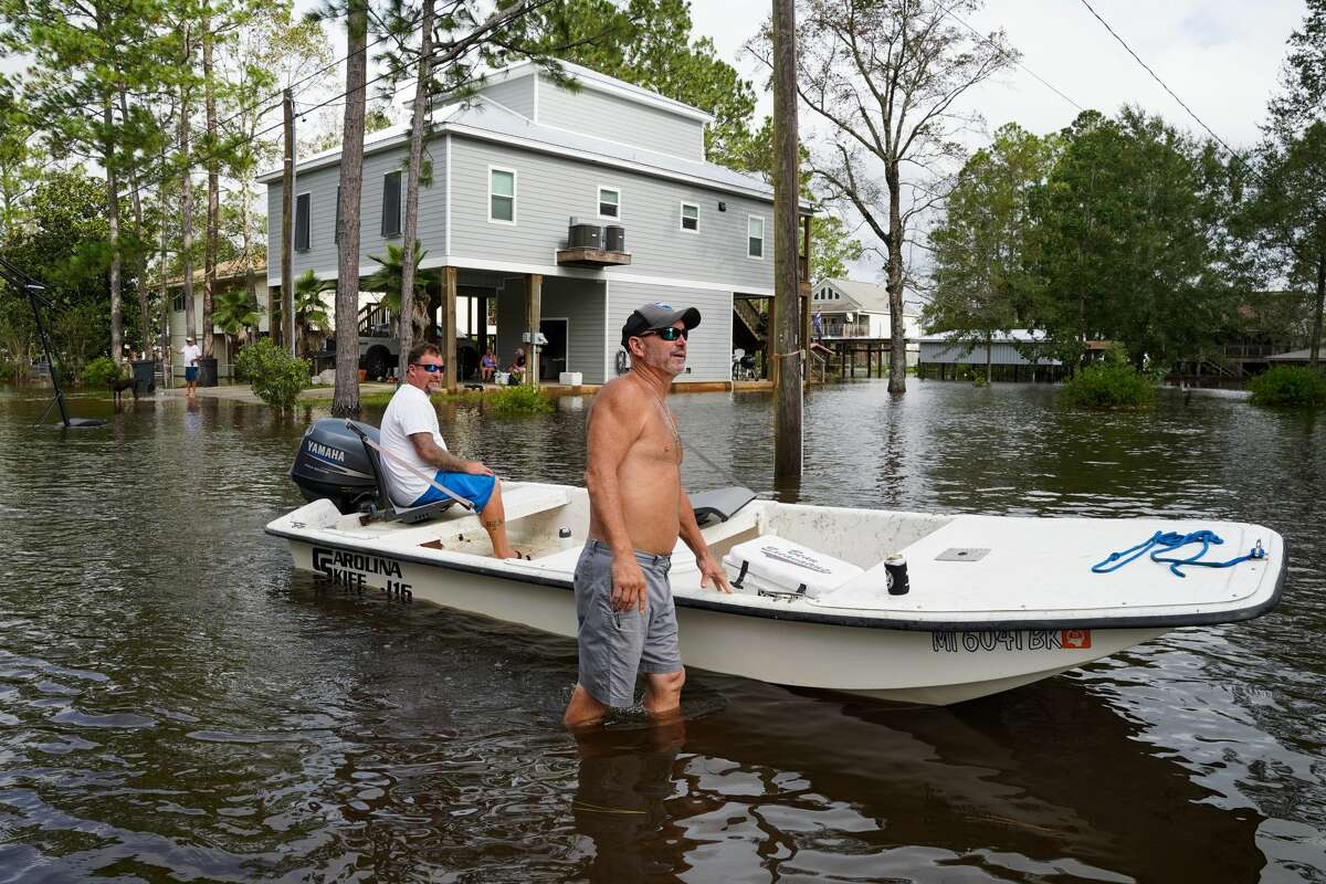 Jay Warner, left,and Mike Bilbo use a boat in their flooded neighborhood on August 30, 2021 in Kiln, Mississippi. Tropical Storm Ida made landfall as a Category 4 hurricane yesterday in Louisiana and brought flooding and wind damage along the Gulf Coast. The storm is pushing toward upstate New York and meteorologists have issued a flood watch for areas south of Albany.(Photo by Sean Rayford/Getty Images)