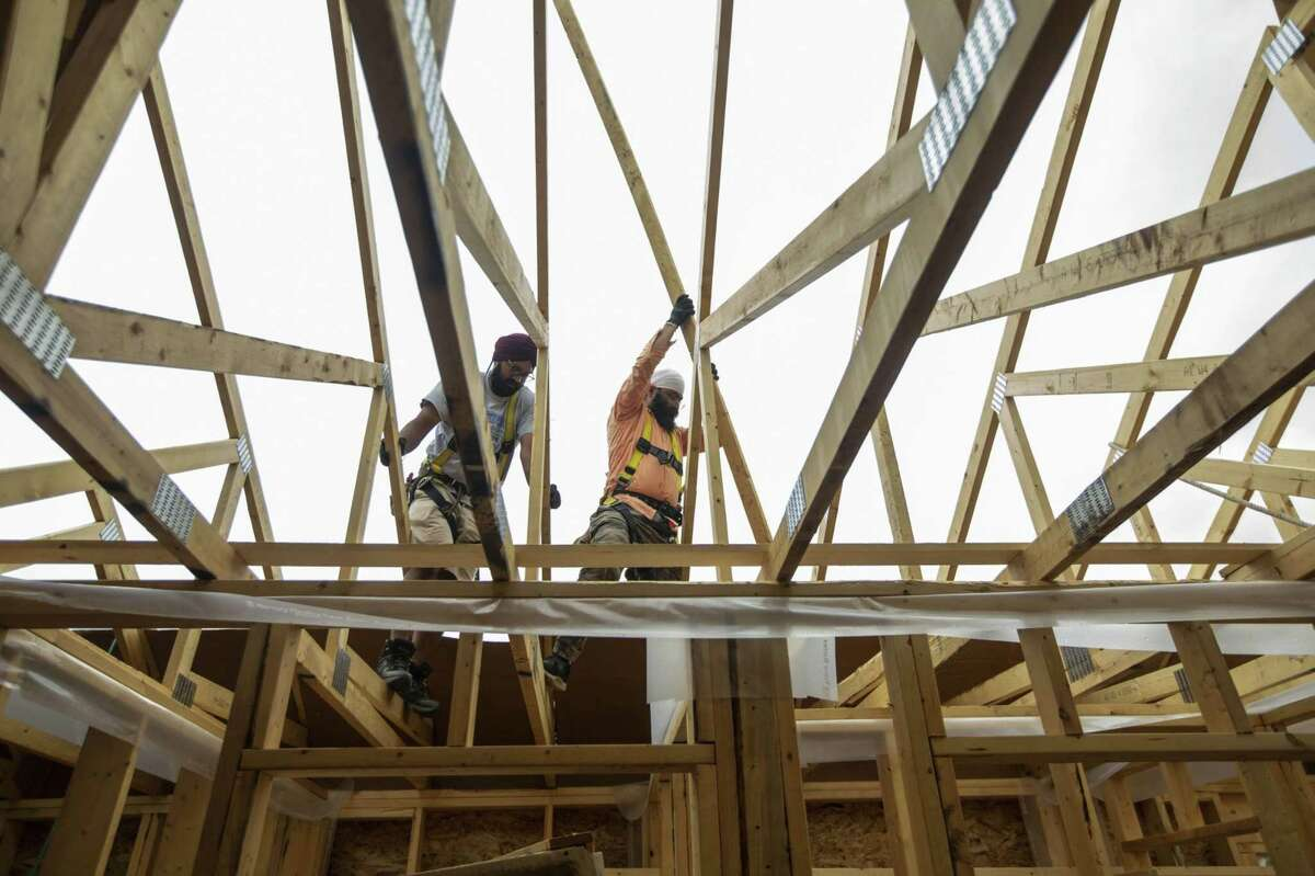 Workers climb through the rafters of a home under construction by Akash Homes in Edmonton, Alberta, Canada, on June 15, 2021.