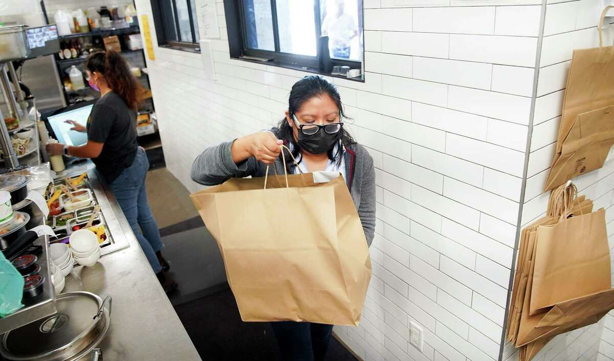 Dish Society floor manager Lorena Herrera takes out a to-go order to a customer during the restaurant's lunch rush in Houston on Monday, Aug. 30, 2021.