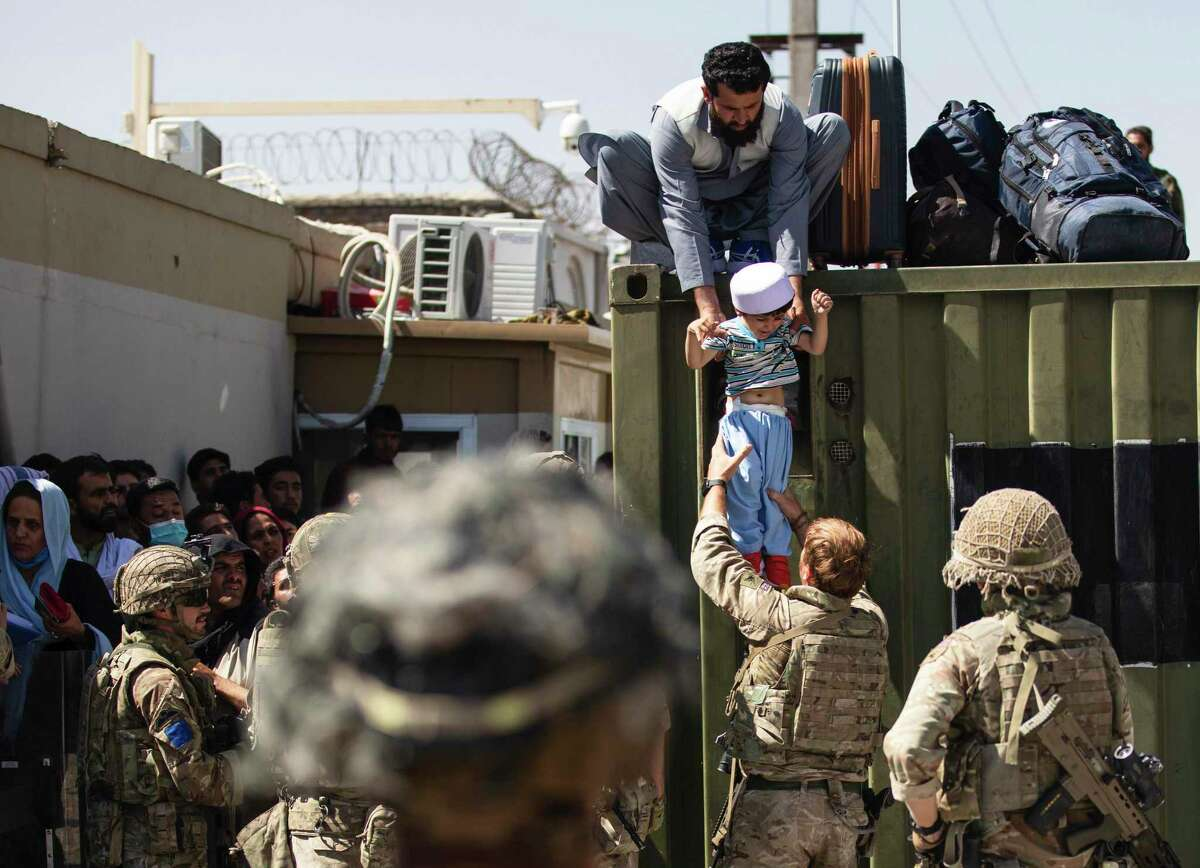 In this image provided by the U.S. Army, an Afghan man hands his child to a British Paratrooper assigned to 2nd Battalion, Parachute Regiment while a member of 1st Brigade Combat Team, 82nd Airborne Division conducts security at Hamid Karzai International Airport in Kabul, Afghanistan, Thursday, Aug 26, 2021. (U.S. Army via AP)