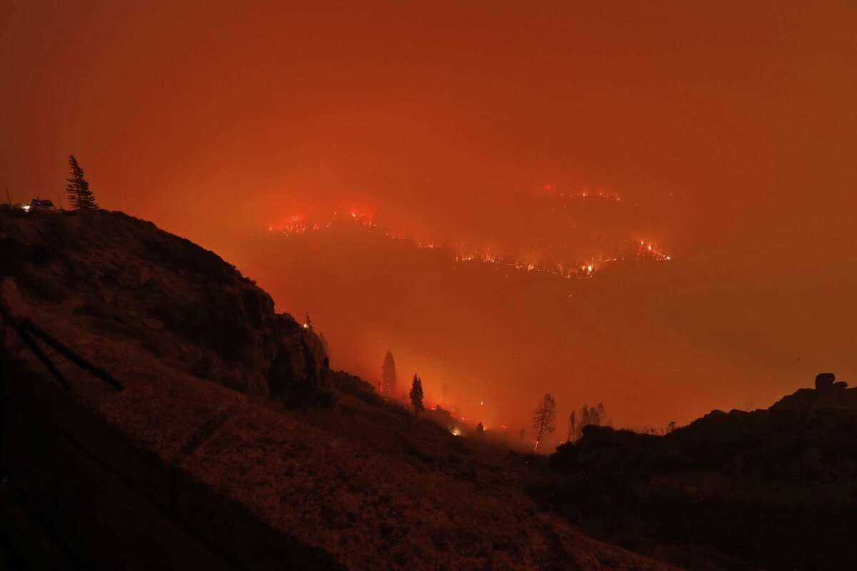 Christmas Valley in the town of Meyers, is seen awash in the glow of flames and smoke as the Caldor Fire encroaches on the community in Meyers, Calif., on Monday.