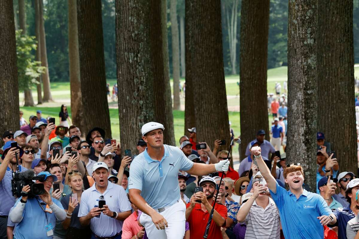 Fans cheer as Bryson DeChambeau of the United States reacts to his second shot on the eighth hole during the third round of the BMW Championship at Caves Valley Golf Club on Aug. 28, 2021, in Owings Mills, Md.