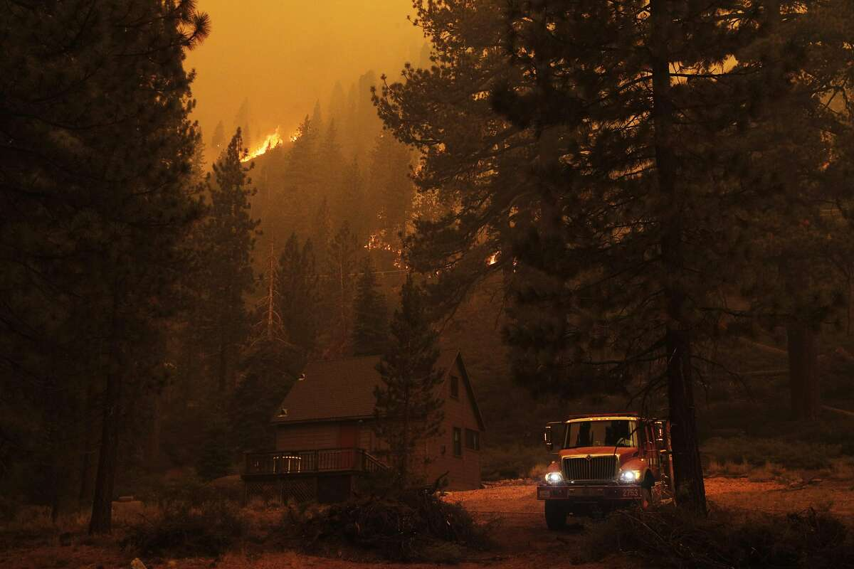 Firefighters working structure protection in Christmas Valley in the town of Meyers work to prevent further devastation left by the Caldor Fire in Meyers, Calif., on Monday, August 30, 2021.