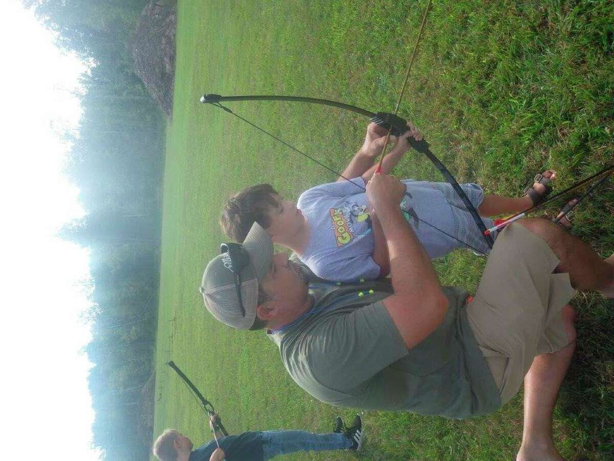 Experienced bowhunter Nick Chippi of Cass City tutors his 8-year-oldson, Wyatt, on the archery range during the recent Free Youth Day at the Cass City Gun Club. (Tom Lounsbury/Hearst Michigan)