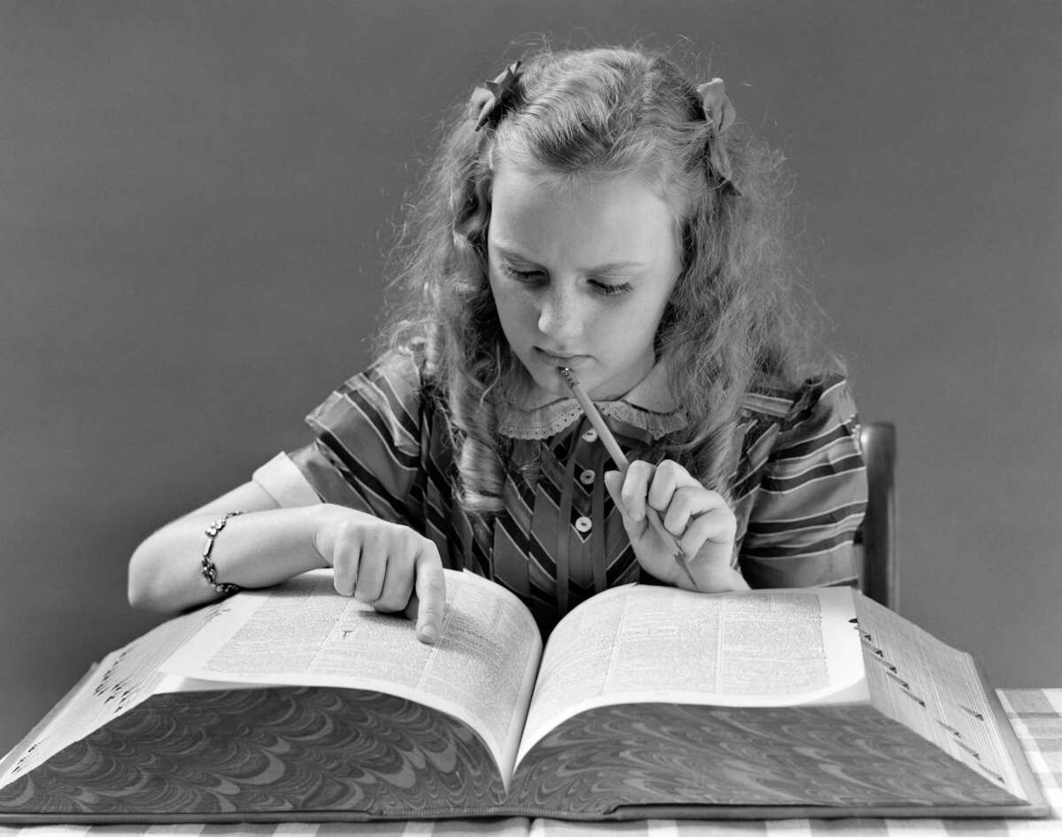 A young girl looks in a dictionary while holding a pencil to her chin. (Photo by H. Armstrong Roberts/ClassicStock/Getty Images)