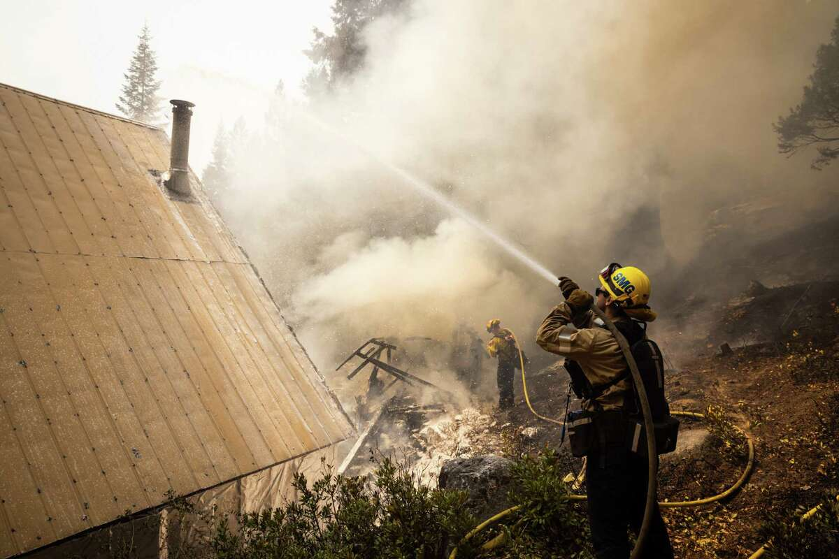 Firefighters work to save a cabin from the raging Caldor Fire in Strawberry, Calif., on Monday, Aug. 30, 2021. Experts say the Caldor Fire is both a cautionary tale for future megafires in the West and one that lays bare a certain futility in attempting to fully control the most aggressive wildfires.