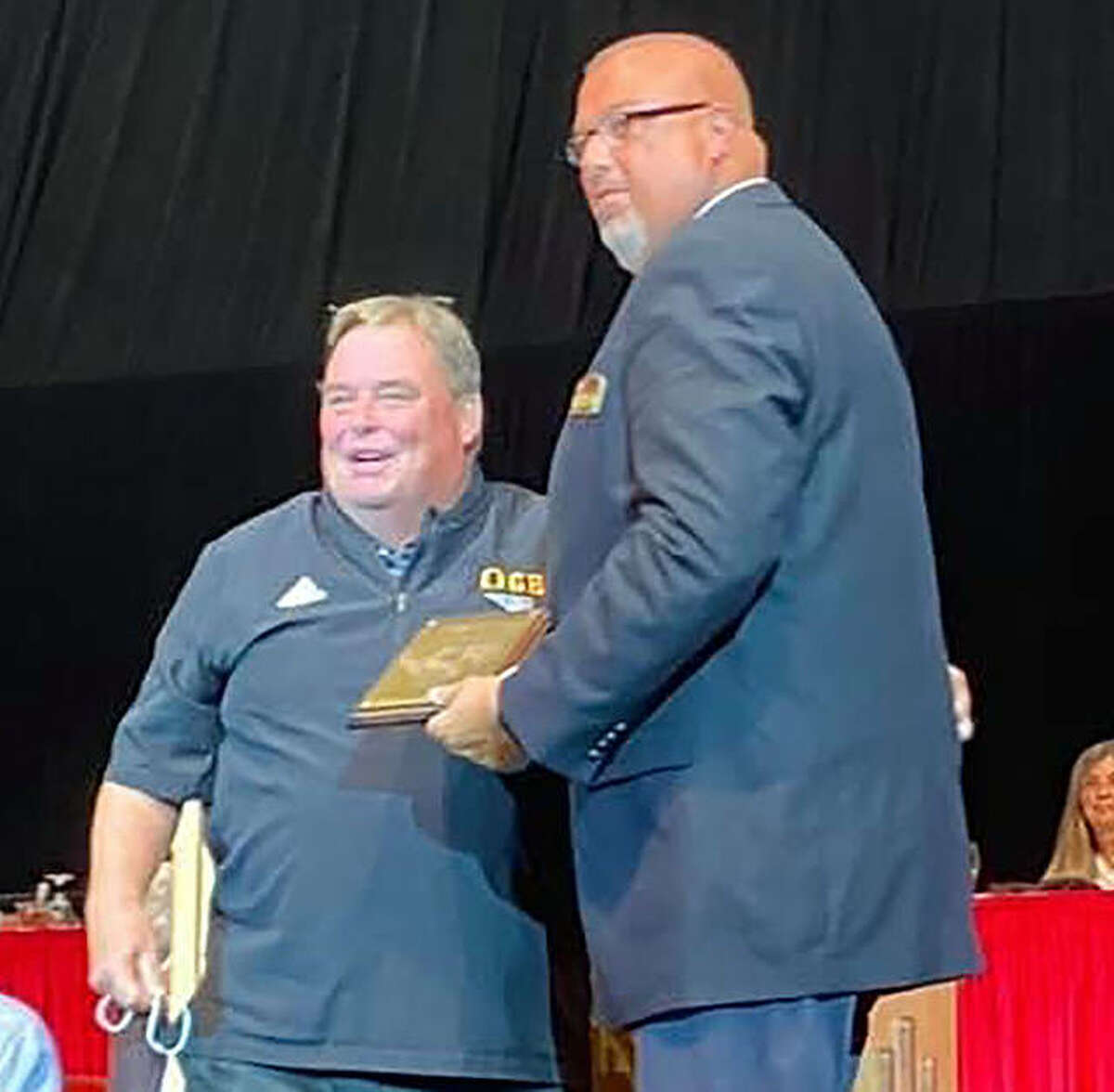 Former East Alton-Wood river head basketball coach Joe Parmentier, left, receives his Illinois Basketball Coaches Association Hall of Fame Plaque from Jeff Abell, who once was an assistant coach under Parmentier. The induction ceremony took place Saturday night at Redbird Arena at Illinois State University in Normal. Parmentier also coached basketball at Concord Triopia and at Mount Olive prior to going to EA-WR.