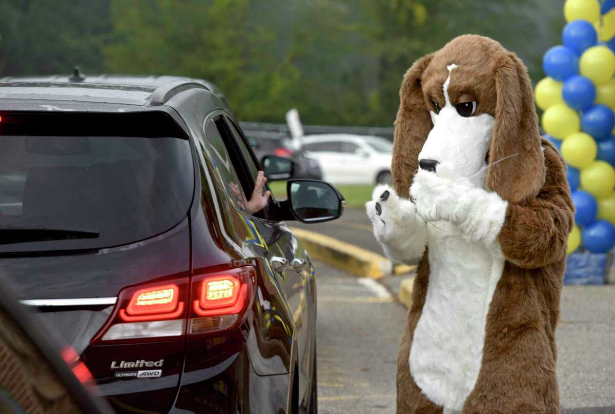 Huckleberry Hound, the school mascot, waves to a student being dropped off for the first day of new school year at Huckleberry Hill School. Head custodian Greg Prendi is inside the hound suit. Brookfield, Conn. Tuesday, August 31, 2021.