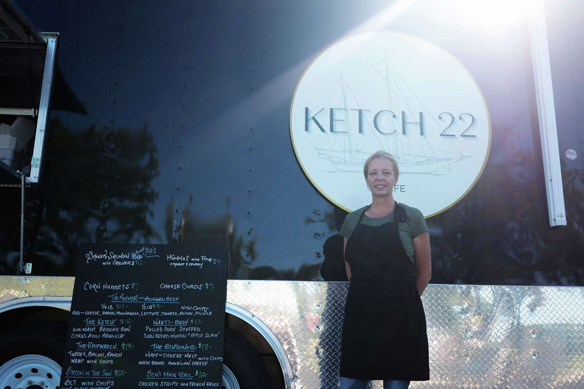 Brandy Stoops stands in front of the Ketch-22 food truck and alongside the menu at the Arcadia location on M-22/State Street.