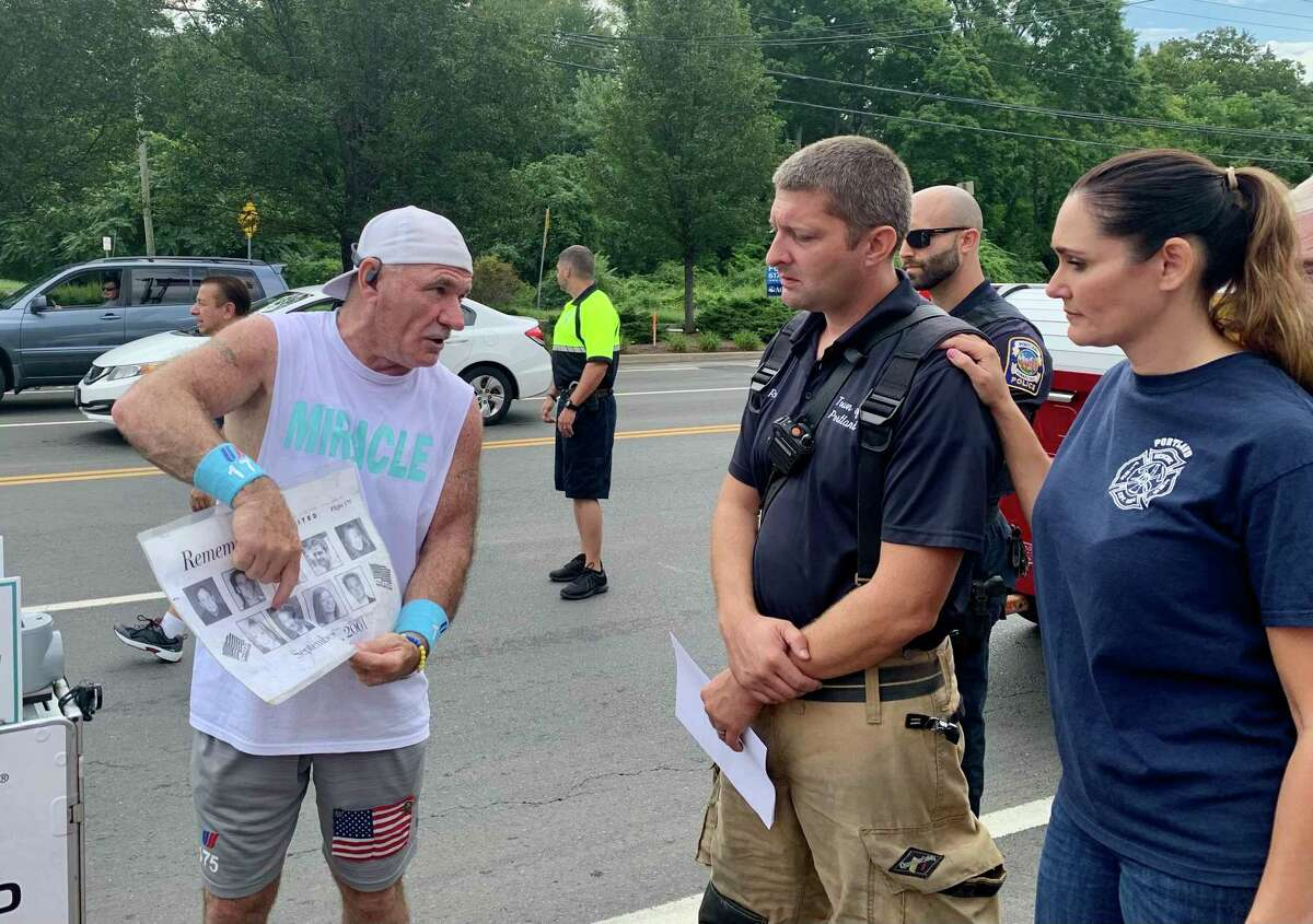 Paul Veneto speaks with Portland Deputy Fire Chief Rob Puida and his wife, Kimberly Puida, Tuesday about the crew members of Flight 175 he had worked with prior to 9/11.