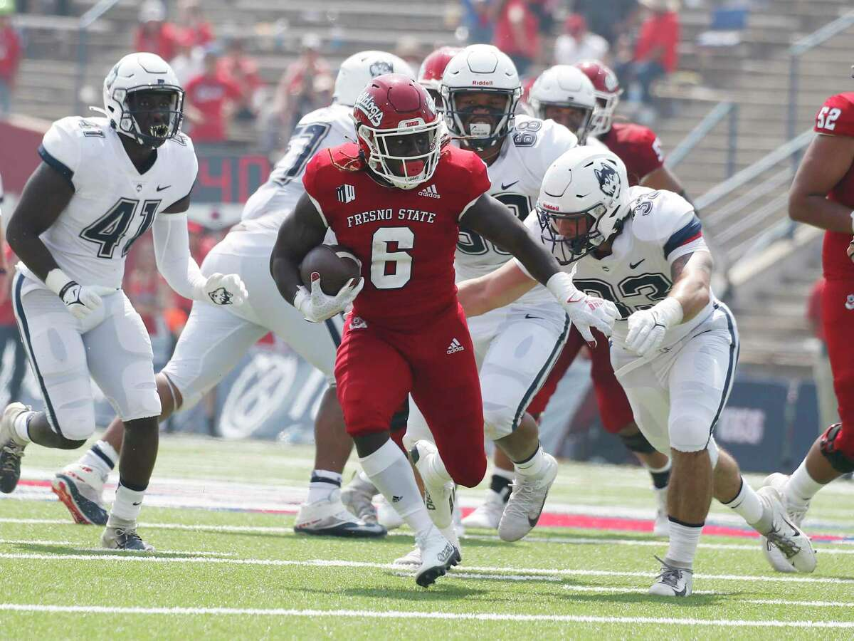Fresno State running back Jordan Wilmore is chased by UConn linebacker Hunter Webb during the second half of an NCAA football game in Fresno, Calif., on Aug. 28.
