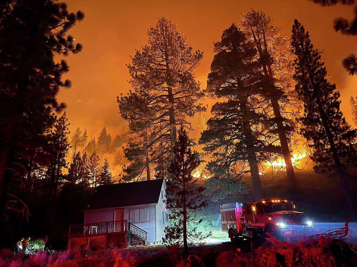 Firefighters protect a home from the Caldor Fire off of S. Upper Truckee Road in the Christmas Valley area of the Tahoe Basin, Monday evening, Aug. 30, 2021, near South Lake Tahoe, Calif. (Elias Funez/The Union via AP)