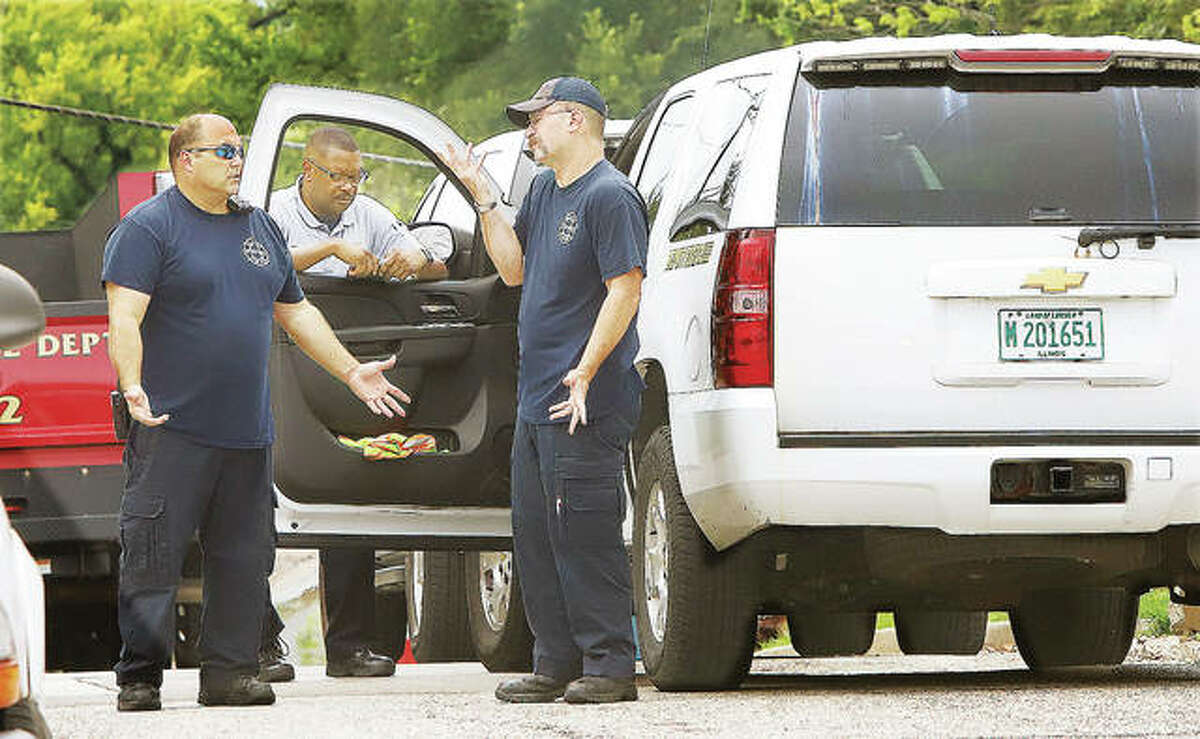 Alton firefighters and elements of the department's command structure, including Chief Jesse Jemison, center, have a conversation Tuesday at the scene of an investigation on Park Drive.