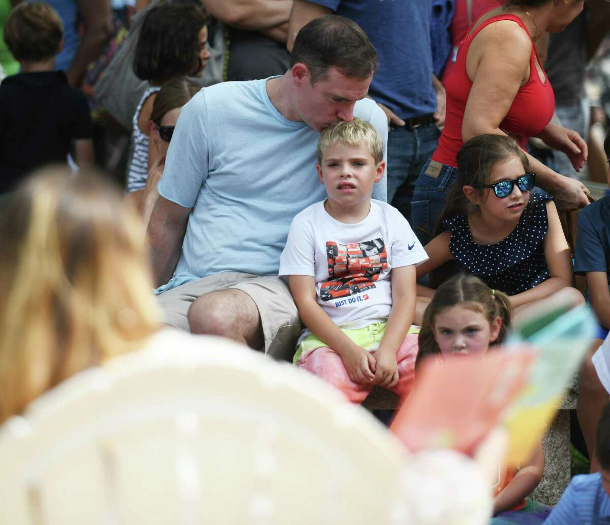 Peter Devine and his kindergartener, Julian, listen during Back to School Story Hour at Old Greenwich School in Old Greenwich, Conn. Tuesday, Aug. 31, 2021. Students and parents enjoyed storytime and an ice cream picnic and outdoors before the start of the 2021-2022 school year.