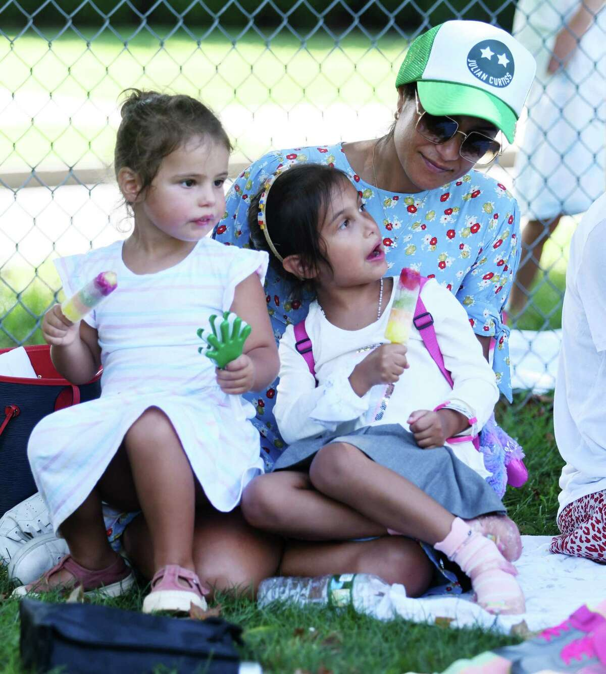 Anthea Rushing relaxes in the shade with her kids Loulou Belle, left, 3, and Tigerlily, entering kindergarten, at the Welcome Back Picnic at Julian Curtiss School in Greenwich, Conn. Tuesday, Aug. 31, 2021. Students and parents enjoyed a picnic and outdoor games the day before the start of the 2021-2022 school year.