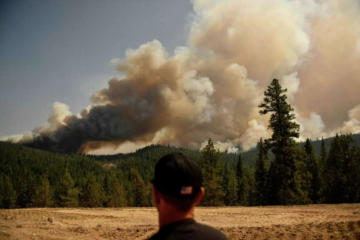 A firefighter looks from Fredonyer Pass on Aug. 18 as smoke plumes from spot fires rise during the Dixie Fire near Susanville (Lassen County). The wildfire has burned 800,000-plus acres, according to Cal Fire.
