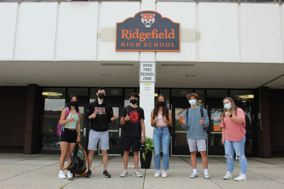 From left: Ridgefield High School students Hannah Yu, Matthew Uy, Jack Federici, Charlotte Kemp, Jackson Fiore and Lizzy Garson give a thumbs up before reporting to class on the first day of school.