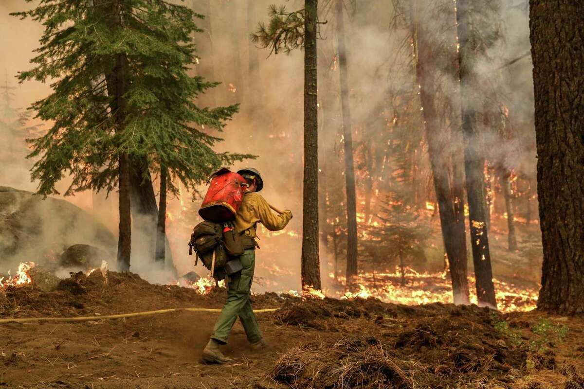 An El Dorado hot shot crew member walks toward a property while monitoring a blaze from the Caldor Fire in Meyers (El Dorado County).