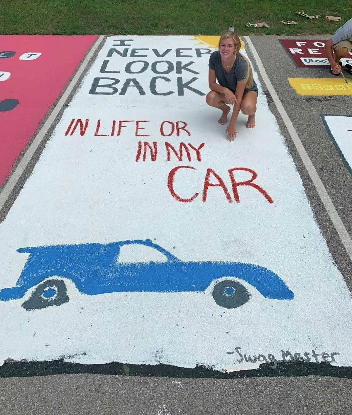 Onekama High School senior Kaylin Sam shows off her parking space at the school on Saturday. (Courtesy photo)