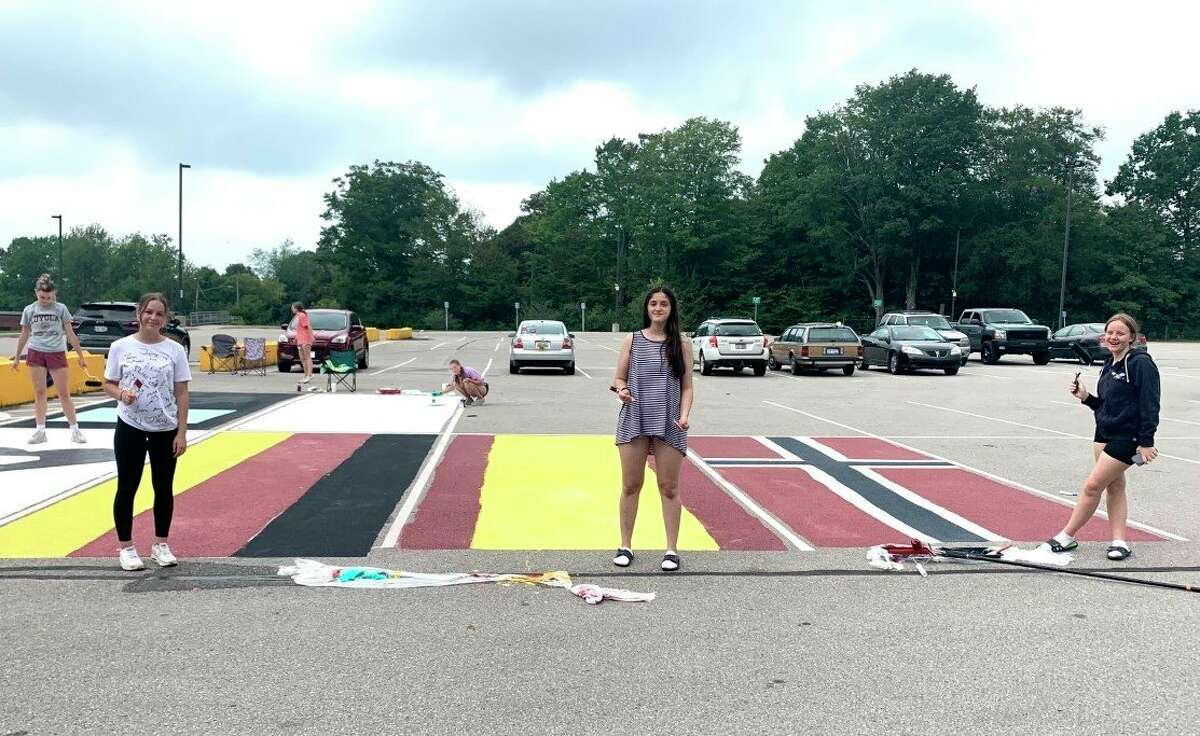 Onekama High School foreign exchange students Carla, Raquel and Martine pose for a photo in front of the parking spaces they decorated by painting the flags of their home countries. (Courtesy photo)