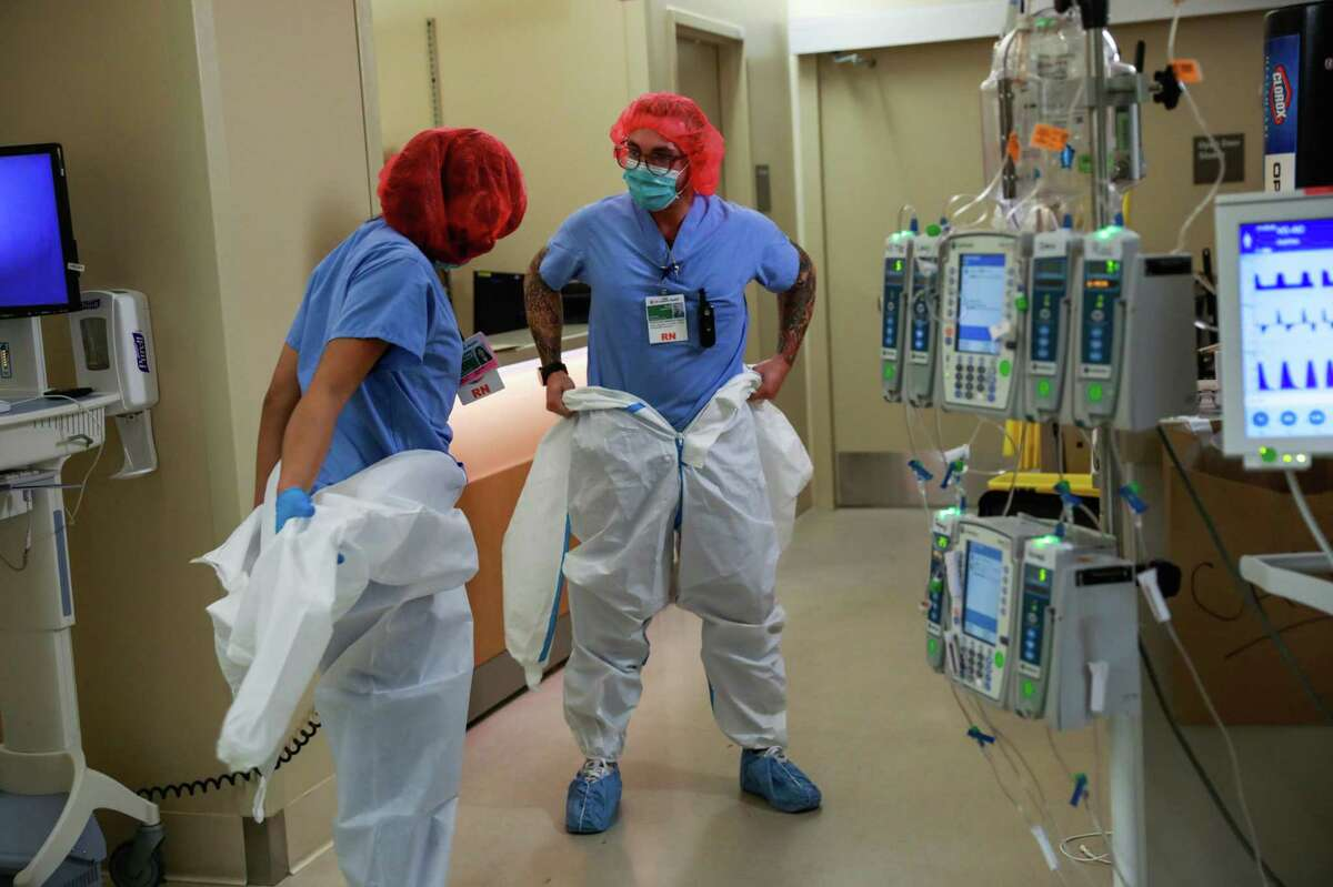 Nurses Casey Cabanas (left) and Scott Lawrence don protective gear to enter a negative pressure room where they take care of COVID-19 patients at El Camino Hospital in Mountain View.