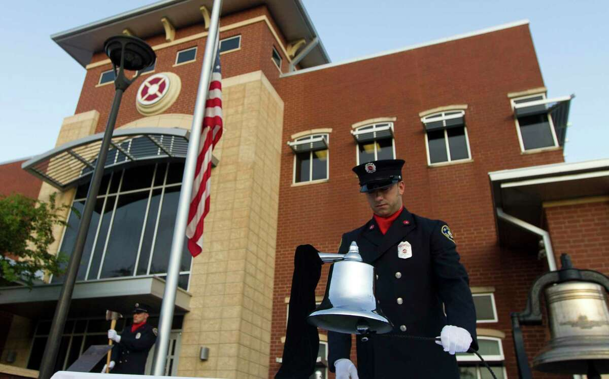 A member of The Woodlands Firefighter honor guard rings a bell in remembrance of the nearly 3,000 victims of the terror attacks on September 11 during a ceremony at The Woodlands Central Fire Station on Sept. 11, 2019.