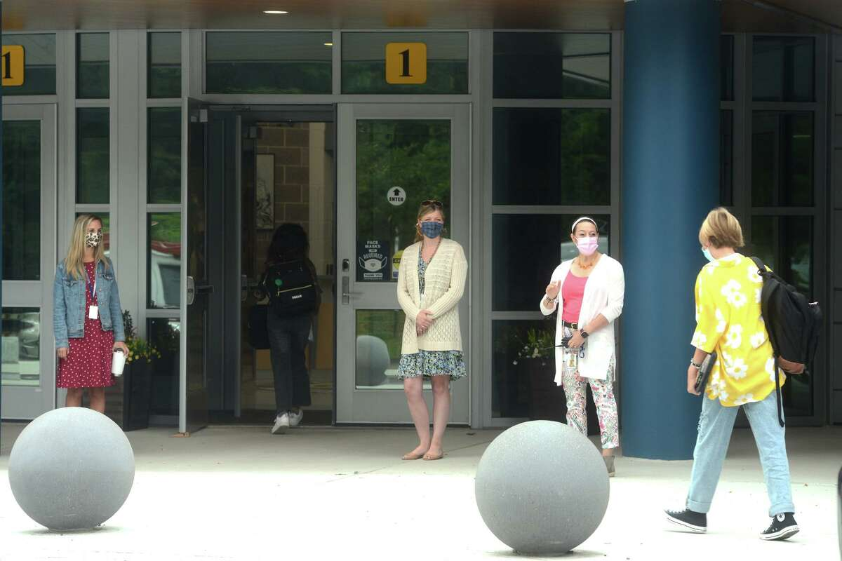 Staff and faculty members wait to greet students on the first day of classes at Coleytown Middle School, in Westport, Conn. Aug. 31, 2021.