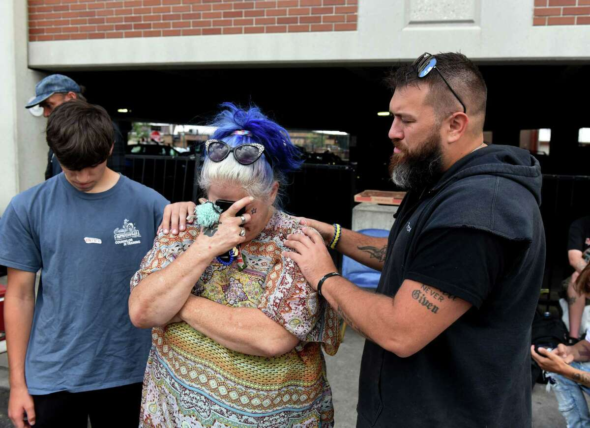 Dave Santy of Mechanicville, right, and his son, Johnathan, left, say a prayer for Julie Stewart, center, during a weekly informal outreach to provide food and support for people who are homeless or in need in Saratoga on Tuesday, Aug. 31, 2021, on Woodlawn Ave. in Saratoga Springs, N.Y.