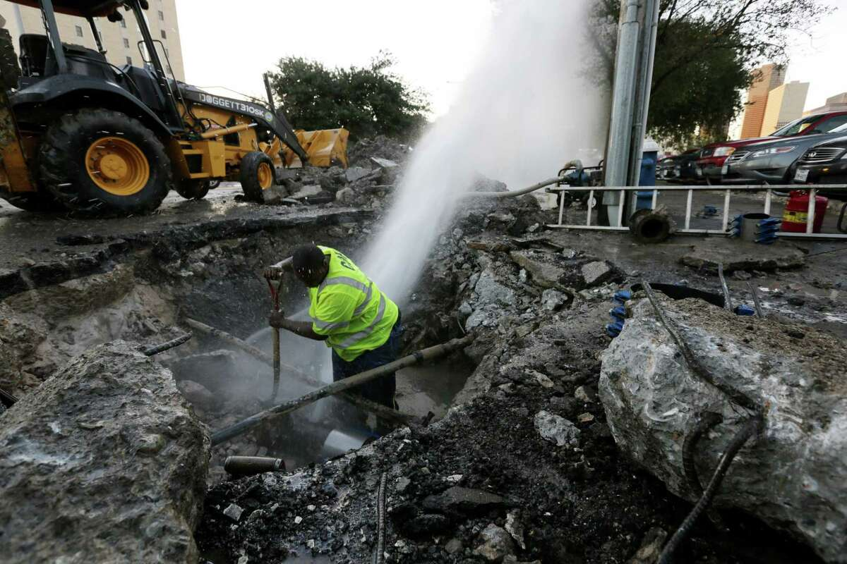 A city worker tries to repair a broken water main line on Leeland Street in 2015. The city says aging infrastructure is one reason it substantially raised water rates, which take effect Wednesday.