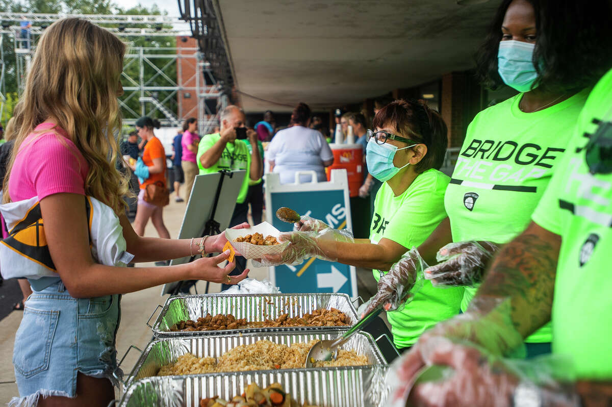 """Mary Linda Fisher, right, serves a plate of food to Lauren Shuart, left, during the """"Feed the City"""" event hosted by Bridge the Gap Tuesday, Aug. 31, 2021 at Midland Center for the Arts. The organization aims to build positive relationships between communities and law enforcement. (Katy Kildee/kkildee@mdn.net)"""