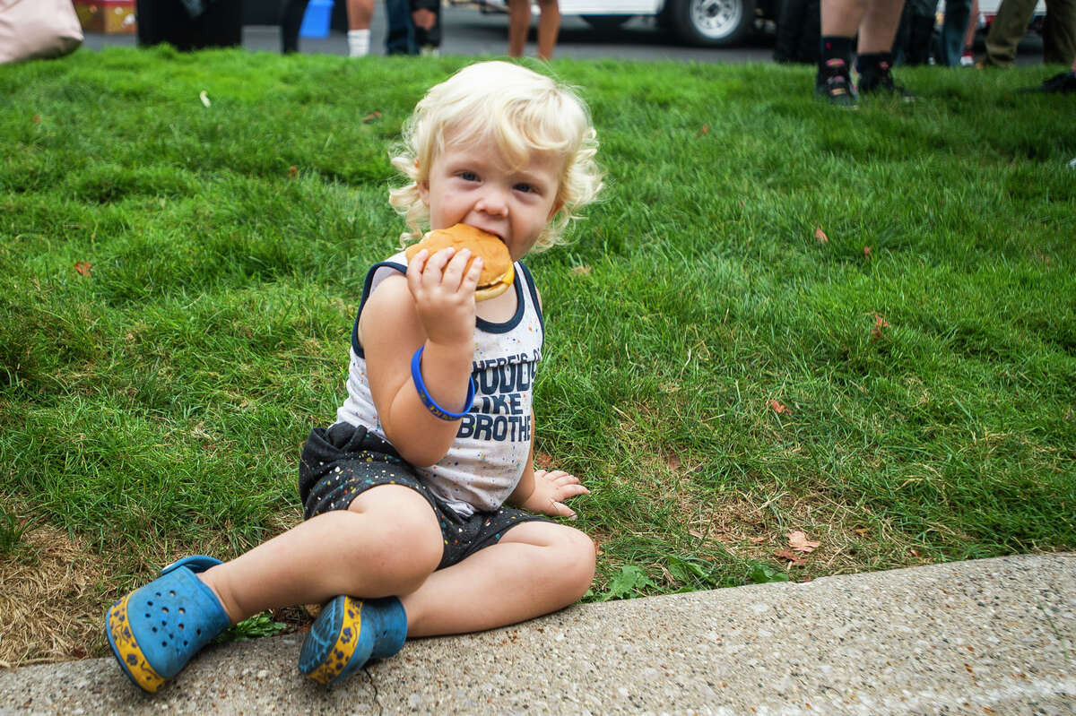"""Chance Hardenburgh of Midland, 2, enjoys a cheeseburger during a """"Feed the City"""" event hosted by Bridge the Gap Tuesday, Aug. 31, 2021 at Midland Center for the Arts. The organization aims to build positive relationships between communities and law enforcement. (Katy Kildee/kkildee@mdn.net)"""