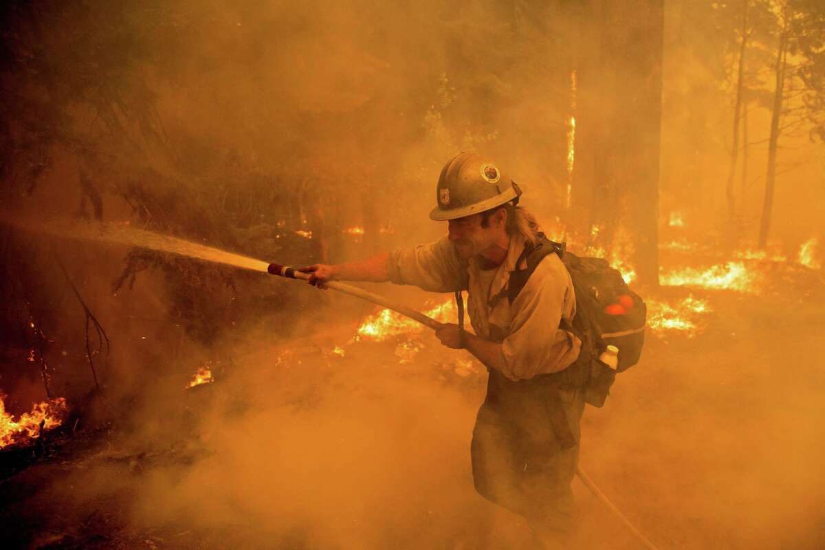 El Dorado Hot Shots crew member Kevin Cisco chokes through the smoke while defending homes in Meyers.