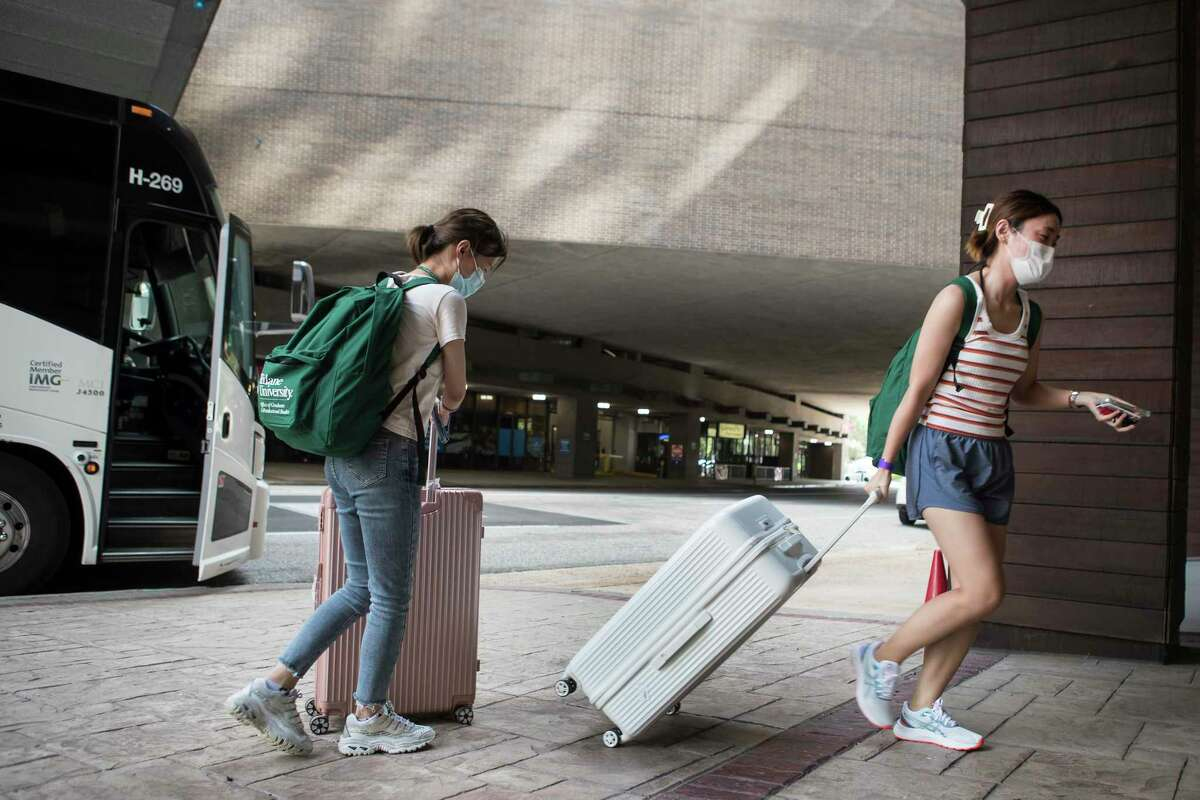 Alba Zhao, a Tulane University graduate student from Beijing, right, is dropped off at the downtown Hyatt after evacuating New Orleans in the aftermath of Hurricane Ida Tuesday, Aug. 31, 2021 in Houston. A total of 1,841 Tulane students were ferried in 35 buses to Houston.