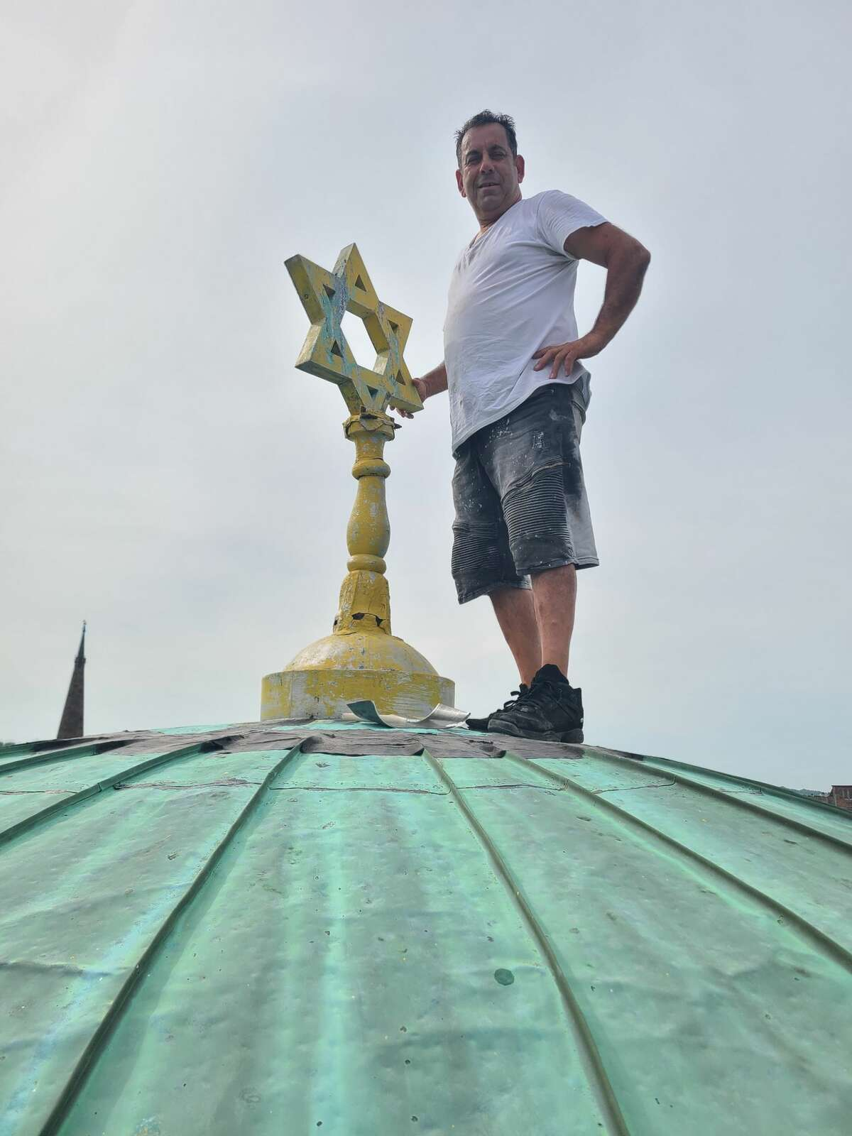A lightning bolt toppled Beth Tephilah synagogue's rusty Star of David. Construction company owner Nick Mamone repaired the leaking roof then put the Star of David, now repainted it's original gold color, atop the dome.
