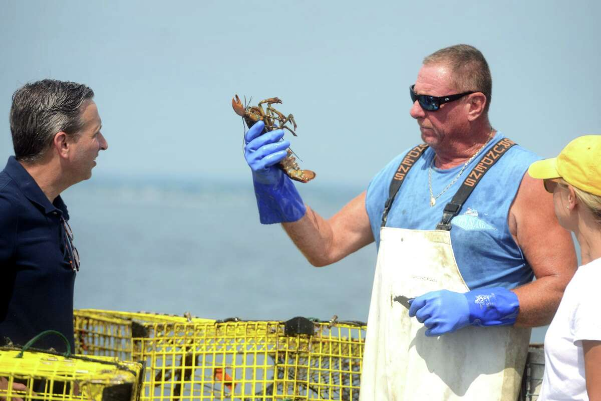 Lobsterman Mike Kalaman speaks with State Sen. Bob Duff onboard the Dark Horse while he pulls up his lobster traps on Long Island Sound, off the coast of Norwalk, Conn. Aug. 31, 2021.