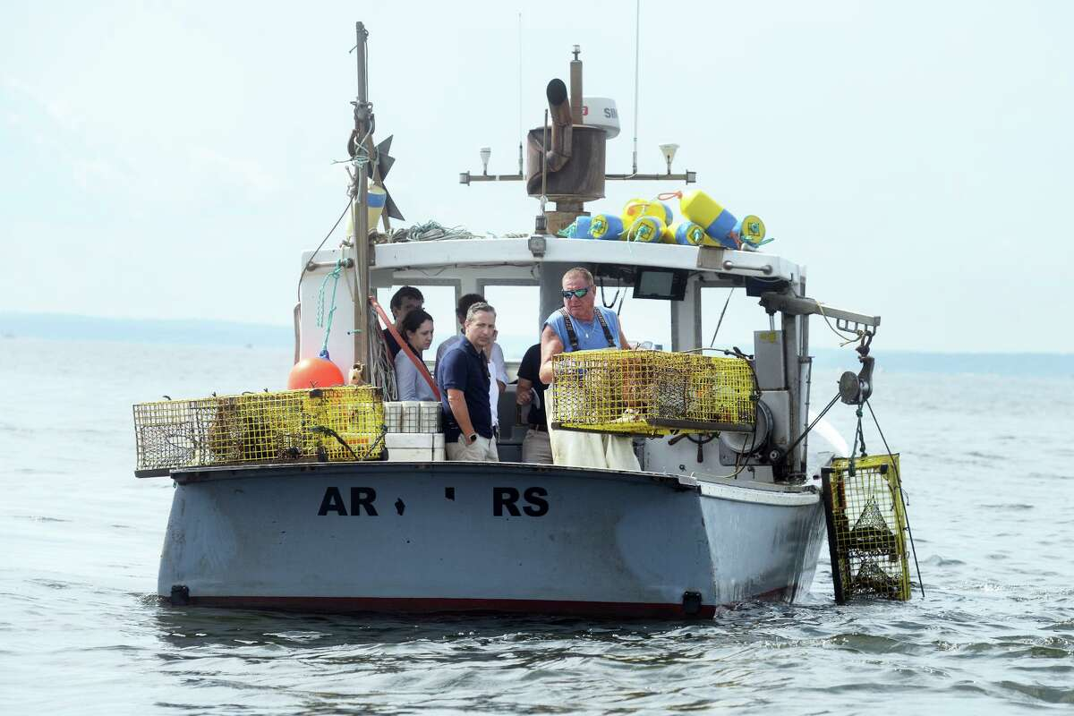 Lobsterman Mike Kalaman pulls in his traps on Long Island Sound, off the coast of Norwalk, Conn. Aug. 31, 2021. Kalaman was joined by a group of state legislators as he made his harvesting rounds on Tuesday.