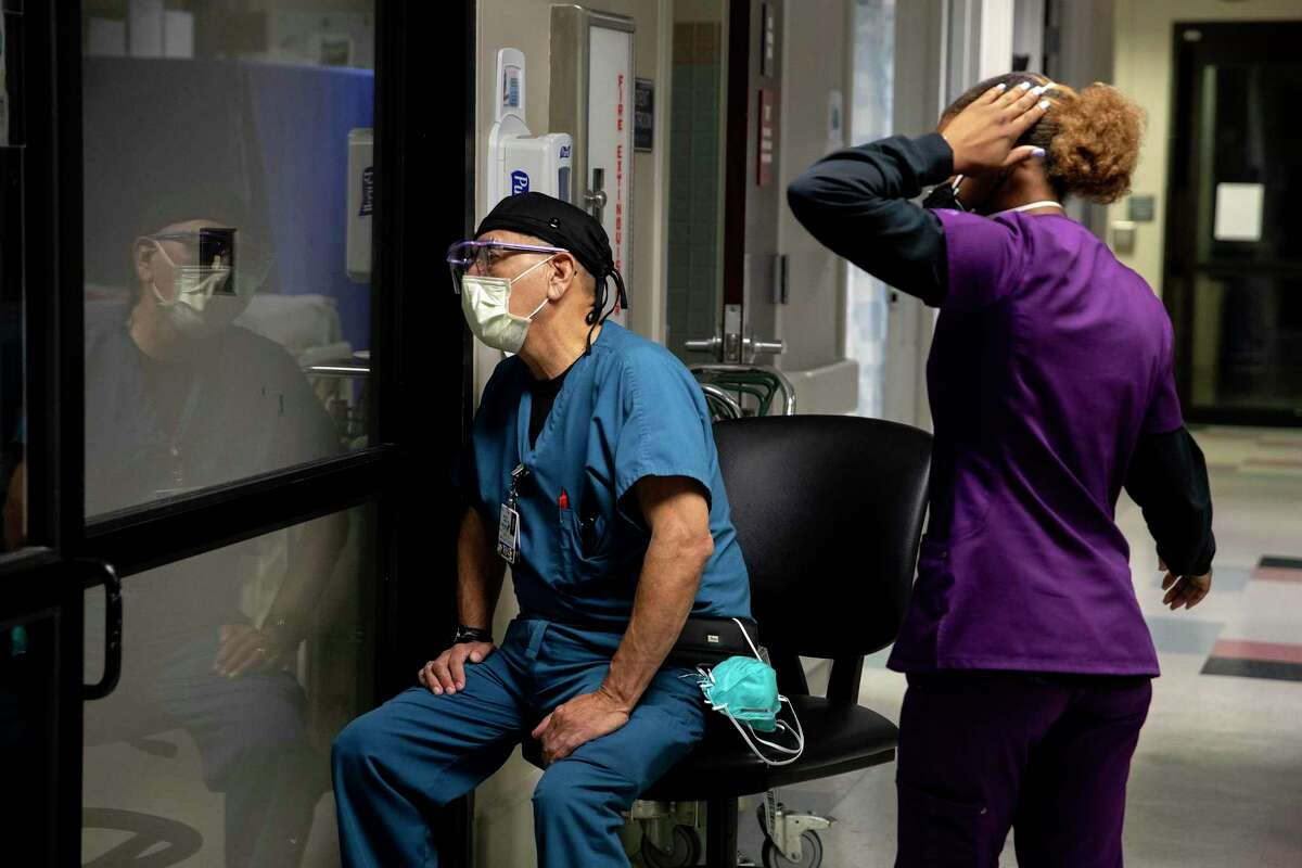 Sabe Upshaw, a patient care technician, and Jose Moreno, a nurse, check on a COVID-19 patient through a window at Texas Vista Medical Center.